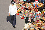 A man in a suit and wearing a black fedora walking through the Souk in Marrakesh, Morocco.