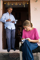 Fairtrade personnel Markus and Melanie Durr take notes while interviewing Fairtrade cotton farmers in their farm house in Maheshwar, Khargone, Madhya Pradesh, India on 13 November 2014. Photo by Suzanne Lee for Fairtrade