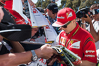 March 13, 2014: Kimi Raikkonen (FIN) from the Scuderia Ferrari team signs autographs at the 2014 Australian Formula One Grand Prix at Albert Park, Melbourne, Australia. Photo Sydney Low.