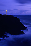 Northhead Ilwaco lighthouse at sunset along the Washington coastline Pacific ocean with rocks and cliff near Ilwaco Washington State USA