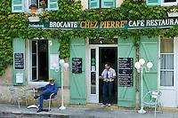 Waiter serves customer Pastis at traditional French Cafe Chez Pierre in Castelmoron d'Albret in Bordeaux region, Gironde, France