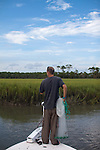 Fisherman with cast net in a tidal creek with marsh grass