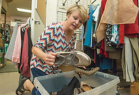 NWA Democrat-Gazette/BEN GOFF @NWABENGOFF<br /> Gwen Shankle of Springdale, who volunteers as a image consultant, sorts donated shoes Saturday, Aug. 4, 2018, during a 'Suit Sorting Saturday' at Dress for Success Northwest Arkansas in Frisco Station Mall in Rogers. Dress for Success, with an additional boutique in Springdale, helps empower women entering the workforce by providing support, classes and appropriate professional attire free of charge. Their clients are referred to them from other area organizations, and include women trying to overcome poverty, new citizens and those returning to society after being incarcerated. Volunteers gather once a month at the Rogers location for a Suit Sorting Saturday to help with intake, sorting, cleaning and repair of donated clothing. The organization plans to hold their annual inventory reduction sale Aug. 25., which is open to the general public and helps fund the organization.