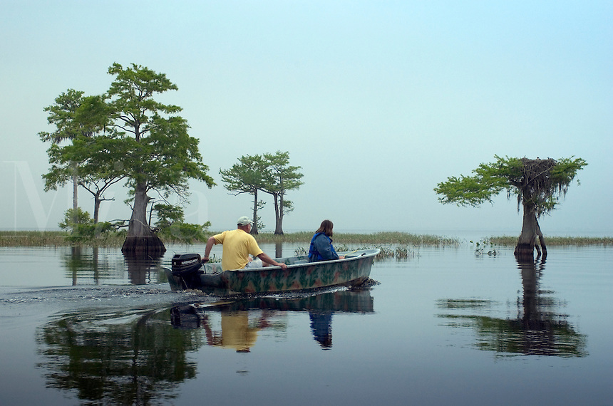 A model released image of a father and his daughter touring  Blue Cypress Lake in a motor boat west of Vero Beach, Florida on a foggy morning in April looking for wildlife. M
