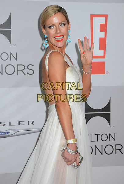 Kathleen Robertson.NBC Universal Golden Globes After Party held at the Beverly Hilton Hotel, Hollywood, California, USA..January 15th, 2012.half length white dress backless side bracelet turquoise dangling earrings red lipstick clutch bag smiling hand waving .CAP/ADM/BT.©Birdie Thompson/AdMedia/Capital Pictures.