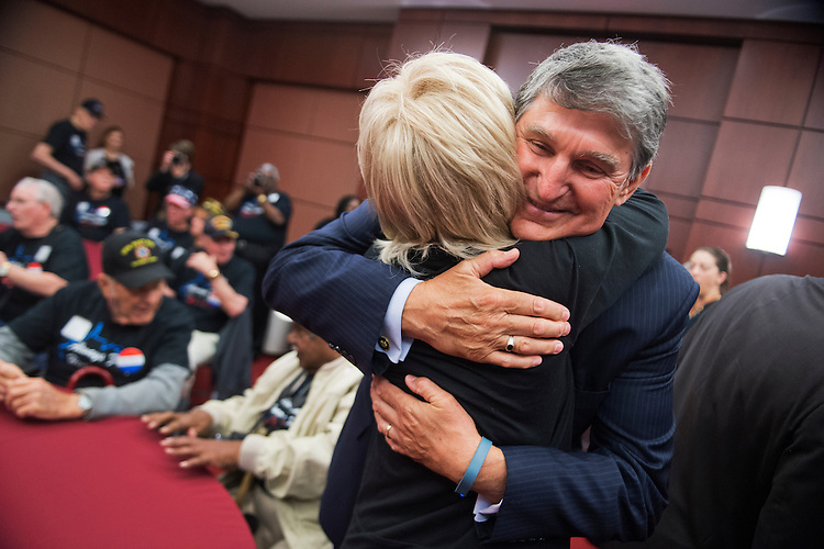 UNITED STATES - MAY 20: Sen. Joe Manchin, D-W.Va., hugs Dreama Denver, of Always Free Honor Flight, during a luncheon in the Capitol Visitor Center for Sgt. John M. Watson, 96, of Beckley, W.Va., who received a Congressional Gold Medal and was recognized by the Tuskegee Airmen Association, May 20, 2015. (Photo By Tom Williams/CQ Roll Call)