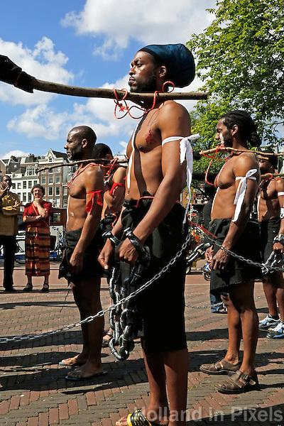 Amsterdam-  Keti Koti. Jaarlijkse viering van de afschaffing van de slavernij. Optocht in klederdracht door de stad. In de stoet lopen ook mannen mee  als geketende slaven
