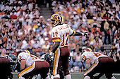 Washington Redskins quarterback Doug Williams directs the offense against the Philadelphia Eagles at RFK Stadium in Washington, D.C. on September 13, 1987.  The Redskins won the game 24 - 14.  Pictured with Williams are center Jeff Bostic (53) and right guard R.C. Thielemann (69).<br /> Credit: Ron Sachs / CNP