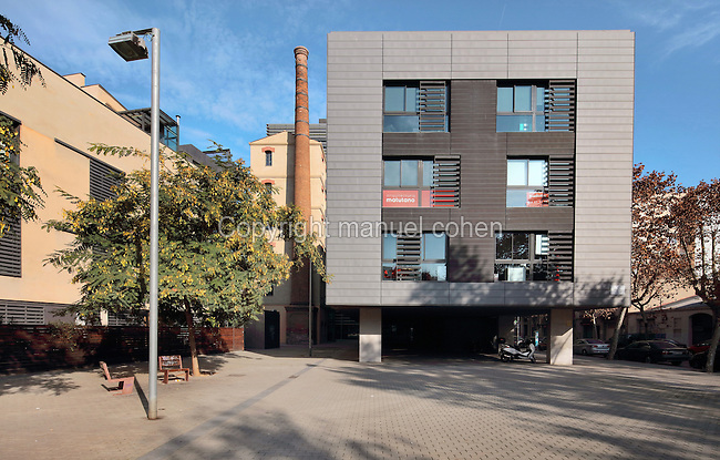 Placa de Merce Sala, with old factories converted into apartment buildings and offices, in the El Poblenou district of Barcelona, Catalonia, Spain. The industrial neighbourhood fell into decline after the Industrial Revolution, and has recently been redeveloped, triggered by the Olympic Games of 1992, resulting in a vibrant, young and artistic community. Picture by Manuel Cohen