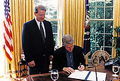 United States President Bill Clinton, with US Vice President Al Gore looking on, signs an Executive Order protecting federal employees and the public from exposure to tobacco smoke in the federal workplace in the Oval Office of the White House in Washington, DC on August 9, 1997.<br /> Mandatory Credit: Barbara Kinney / White House via CNP