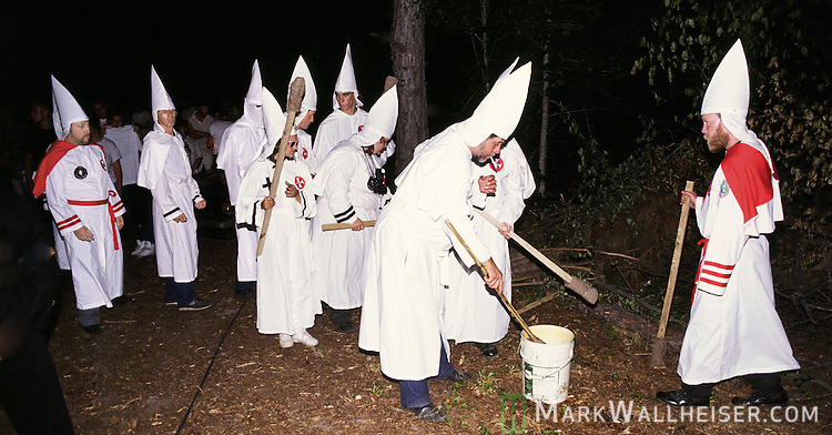 Members of the Invisible Empire of the Knights of the Klu Klux Klan dip their torches for their ceremonial cross lighting in Gadsden County, Florida north of Tallahassee May 26,1990.