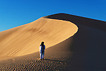 A traditional dressed moroccan man walks up a sand dune.