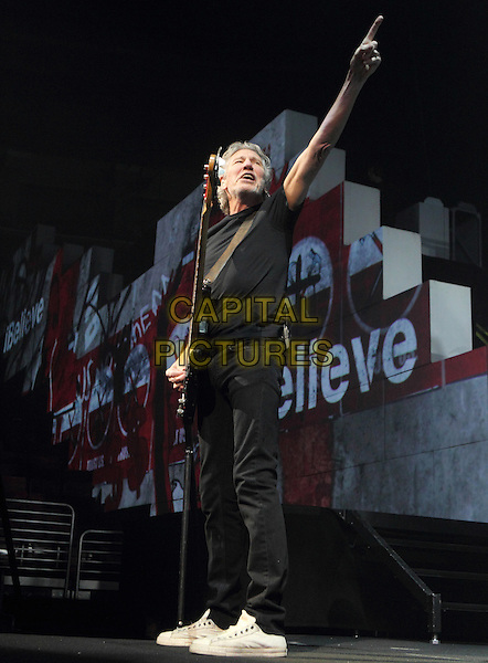 """ROGER WATERS.Roger Waters, original member of Pink Floyd performs """"The Wall"""" at the Wells Fargo Center in Philadelphia, Pennsylvania, USA..November 8th, 2010.stage concert live gig performance music full length black t-shirt guitar jeans denim hand arm pointing.CAP/RKE/EML.©EML/RockinExposures/Capital Pictures."""