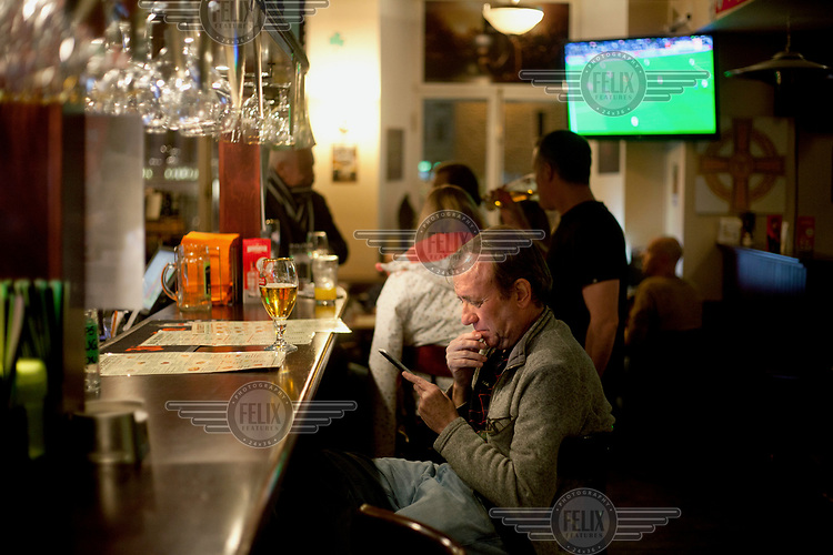 A man checks his smart phone at the bar in Mad Murphy's pub in the old town.