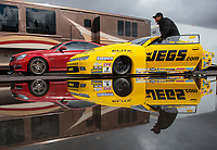 Feb 22, 2019; Chandler, AZ, USA; The car of NHRA pro stock driver Jeg Coughlin Jr reflects in a rain puddle as the car is towed to the staging lanes during qualifying for the Arizona Nationals at Wild Horse Pass Motorsports Park. Mandatory Credit: Mark J. Rebilas-USA TODAY Sports