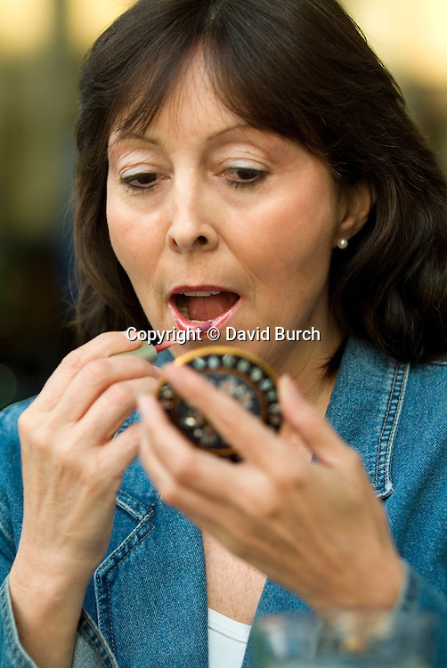 Mature woman applying lipstick, close-up