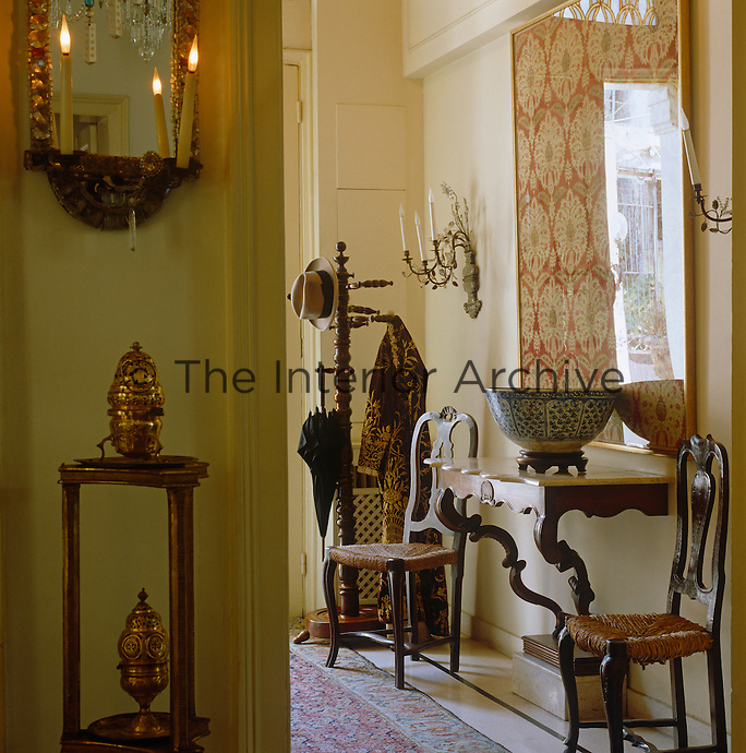 A framed textile hangs above a console table in the entrance hall with a homburg, umbrella and Arab coat on the coat rack