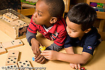 Education Preschool 4-5 year olds boy starting to grab small toy held by another boy who is looking away horizontal