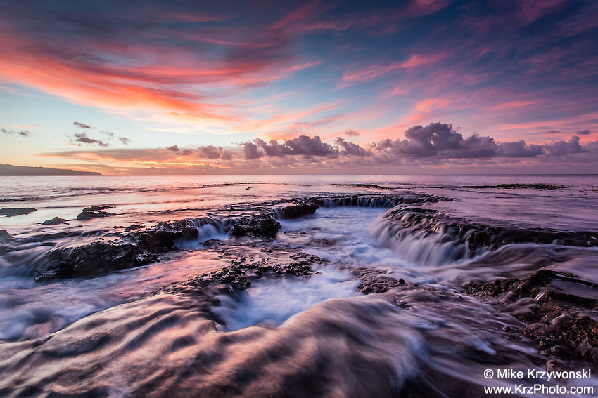 Water cascading off of a rocky shelf under a pink sunset at Shark's Cove, North Shore, Oahu