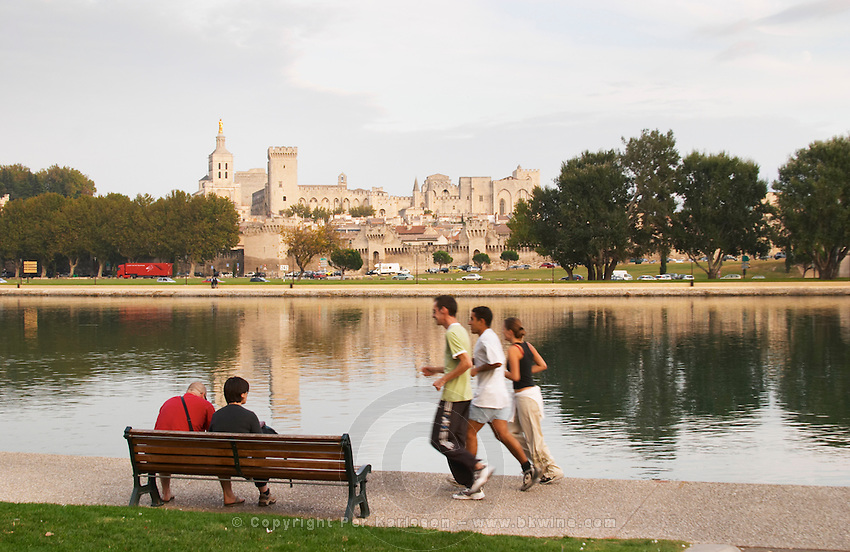 The Pope's palace in Avignon from across the river reflected in the water. A couple sitting on a bench. Three young people running. Avignon, Vaucluse, Provence, Alpes Cote d Azur, France, Europe