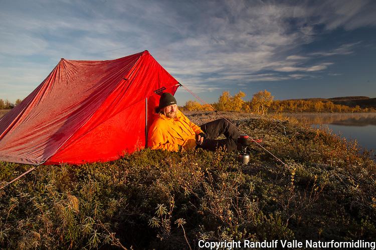 Mann slapper av foran teltet en tidlig høstmorgen. ---- Man relaxing in morning.