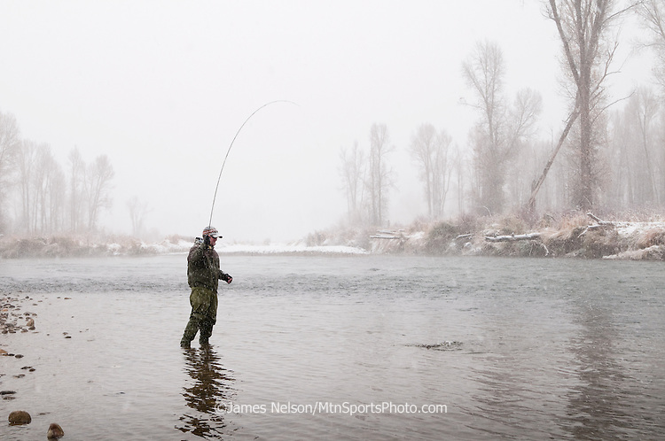 A fly fisherman, Steve Warmann, plays a trout during a snowstorm on the South Fork of the River, Idaho