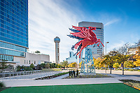 This cityscape image of the Red Flying Neon Horse or Pegasus sitting on top of an oil derrick which rotates for different views. In this image you can see the Reuion Tower and the Omni Hotel. This neon Pegasus had sat on top of the Magnolia Hotel since the 1930 till it had to be taken down because of damage. The neon horse was restore by the Omni Hotel.  This was the orginal symbol of the Magnolia Oil Company