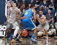 Richard Solomon of California and Justin Cobbs of California wrestle for a loose ball against Kyle Anderson of UCLA during the game at Haas Pavilion in Berkeley, California on February 19th, 2014.  UCLA defeated California, 86-66.