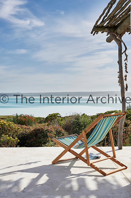 A deck chair with a blue striped fabric seat is placed on a concrete terrace overlooking the sea