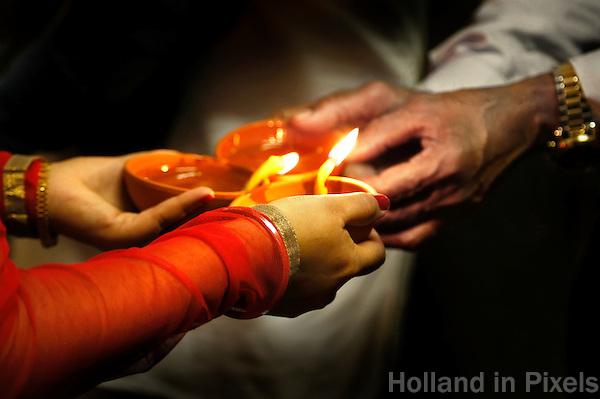 Nederland  Amsterdam. Divali viering in de Shri Guru Nanak Gurdwara Sahib. Bezoekers steken kaarsjes aan.  Foto Berlinda van Dam / Hollandse Hoogte