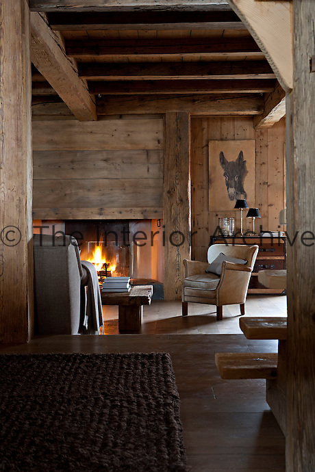 A roaring fire in the first floor living area casts a warm glow around the wood-clad walls of the interior