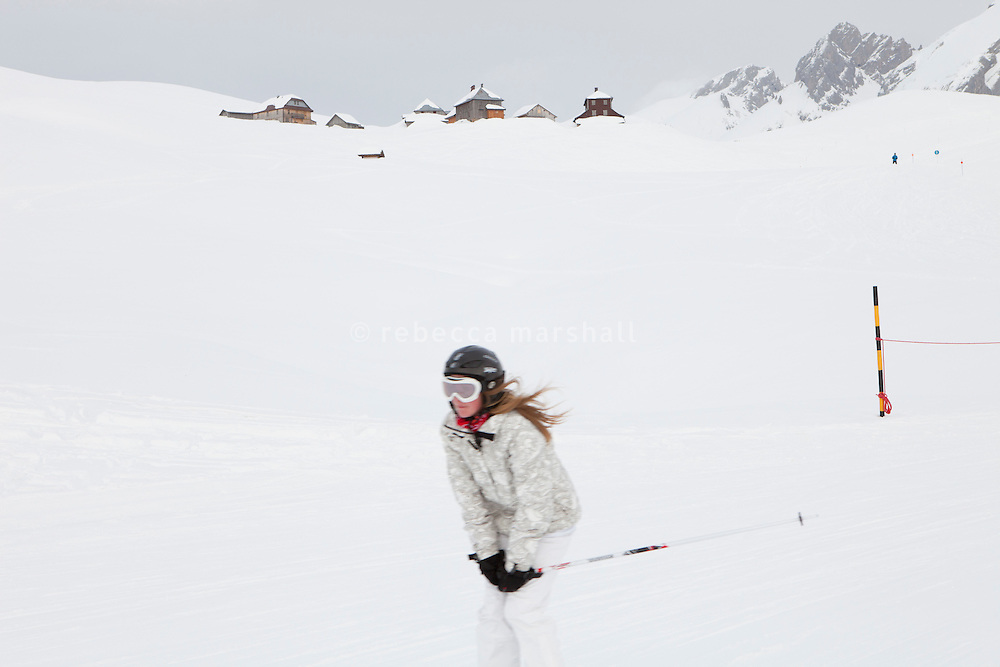 A skier descends the 'La Duche' ski run, near Le Grand Bornand, France, 14 February 2012. Snow-covered chalets can be seen in the background on the Col des Annes.