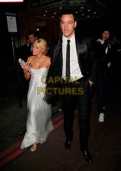 JOHN TERRY & TONI POOLE.At the Cystic Fibrosis Liv Charity Event, Dorchester Hotel,.London, England, February 1st 2008..full length strapless silver white dress black tie suit holding hands couple WAG footballer married husband wife.CAP/CAN.?Can Nguyen/Capital Pictures