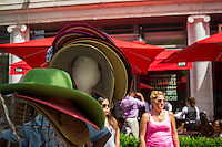 A sidewalk merchant sells women's hats outside the Red Rooster restaurant on Lenox Avenue in the neighborhood of Harlem in New York on Sunday, June 23, 2013. Wide sidewalks and a renaissance in Harlem have caused a number of restaurants to open catering to the more upwardly mobile newer residents. (© Frances M. Roberts)