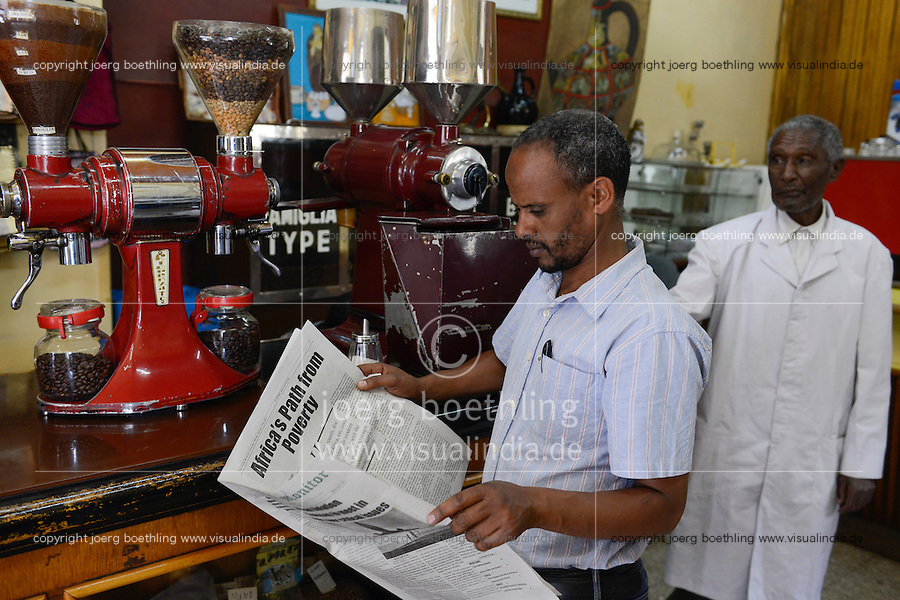 ETHIOPIA, Addis Ababa, Cafe Tomoca, reading the ethiopian newspaper The daily monitor with the headline Africa´s path from poverty / AETHIOPIEN, Addis Abeba, Cafe Tomoca, Zeitung mit Schlagzeile Afrikas Weg aus der Armut