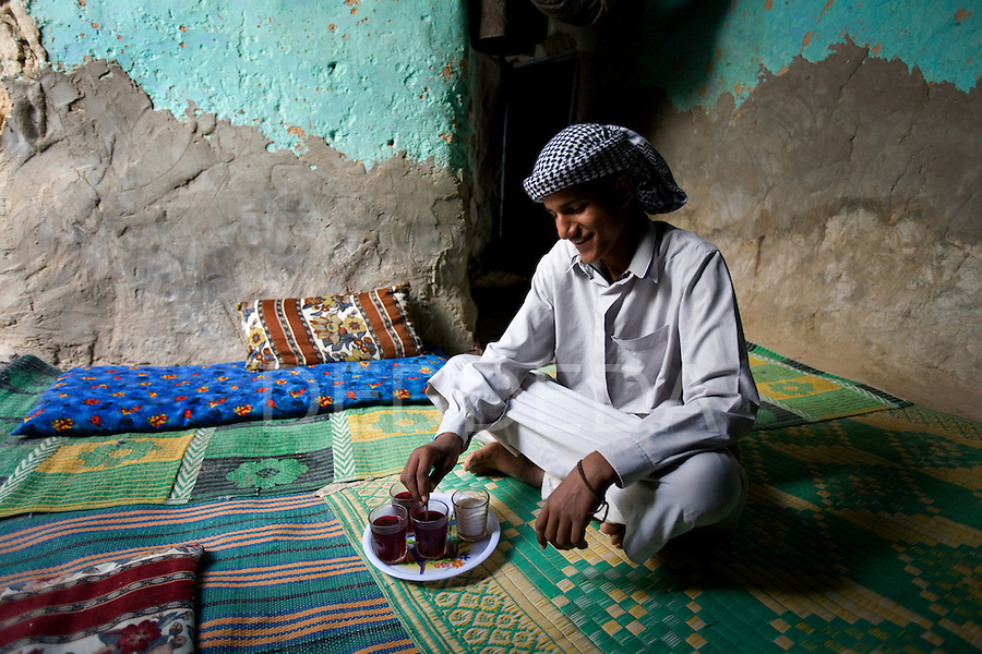 A local Siwan young man dressed in traditional clothing makes hibiscus tea inside his home in Siwa Town of the Siwa Oasis, Egypt.