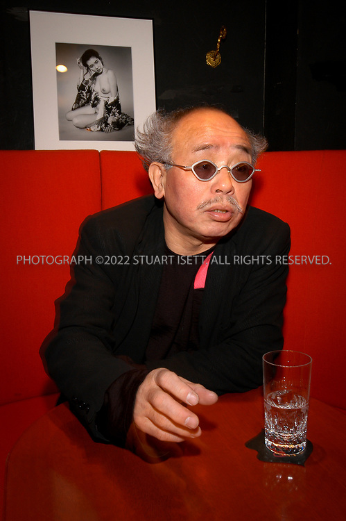 1/30/2003--Tokyo, Japan<br /> <br /> Japanese photographer, Nobuyoshi Araki, speaking under one of his nude portraits taken in the 1980s that hangs in a Tokyo jazz bar. Japan's most famous photographer, Nobuyoshi Araki, 62, is a controversial artist obsessed with rendering women, his one constant focus, as objects. After four decades of prolific output, continual growth and exploration, focused mainly on nudes, flowers his cat and mournful skies, few critics in Japan dispute the artist's appraisal of himself as Tensai Araki, or Araki the Genius. After more that 300 published books, four or five major shows in Japan every year and frequent overseas shows, he is not slowing down nor is he getting bored with his most cherished subject matter, the female form. The photographs of his wife Yoko, who died in 1990, have established his reputation in Japan. Of her he says: Photographing her was everything to me. I shot her more than any other woman, and she was my most exciting subject.<br /> All photographs &copy;2003 Stuart Isett<br /> All rights reserved<br /> This image may not be reproduced without expressed written permission from Stuart Isett.