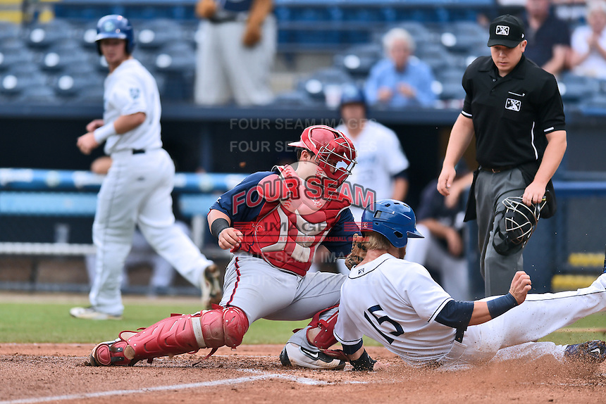 Hagerstown Suns catcher Jorge Tillero (30) fields and applies the tag on Brian Mundell (15) as he slides in safely and home plate umpire Ryan Powers prepares to make the call during a game against the Asheville Tourists at McCormick Field on June 6, 2016 in Asheville, North Carolina. The Tourists defeated the Suns 12-10. (Tony Farlow/Four Seam Images)