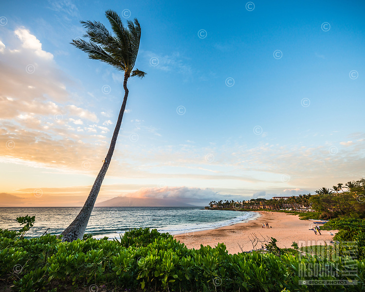 Beachgoers enjoy the sunset along the southern coast of Maui as seen from Wailea.