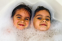 Four year old twin girls taking a bubble bath, Newtown, Connecticut USA