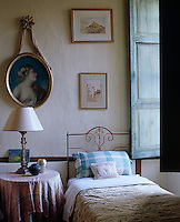 A feminine bedroom with a narrow wrought-iron bed beside the faded shutters of an open window