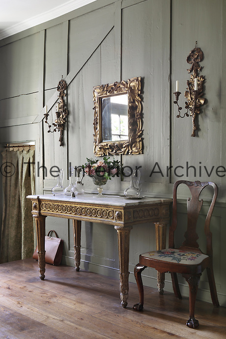 A carved and gilded antique console table stands beside a chair whose needlwork seat was worked by Eleanor Jones