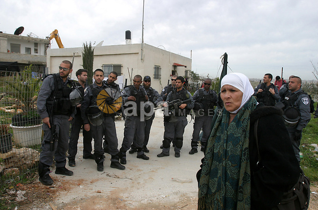 Israeli security forces stand guard as bulldozers destroy a Palestinian house in the Arab east Jerusalem neighborhood of Beit Hanina on February 5, 2013. Palestinian homes built without a construction permit are often demolished by order of the Jerusalem municipality. Photo by Mahfouz Abu Turk