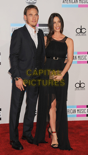 Mario 'Souleye' Treadway & Alanis Morissette.arriving at the 2011 American Music Awards held at Nokia Theatre at L.A. Live in Los Angeles, California, November 20th, 2011.  .arrivals AMA AMAs full length dress couple side fishtail plait braid  sheer gold clutch bag belt .CAP/ROT/TM.©TM/Roth Stock/Capital Pictures