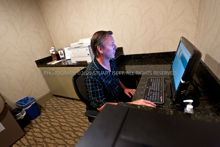 "9/27/2011--Seattle, WA, USA..Don Corbin, 50, from Danville, CA, using the business center, just off the main lobby, at the Silver Cloud Hotel in Seattle, WASH. Corbin was visiting Seattle on vacation so did not have a laptop with him and needed to use the business center to print out boarding passes...Business travelers armed with laptops, smartphones and wifi cards, are eschewing hotel business centers in favor of working in their rooms or the lobby, and hotels across the price spectrum have added the trappings of those business centers to where the guests are.  Hotel business centers are still used by travelers who have a document or boarding pass to print, or need to check email and don't have their laptop, but they will usually get in and out quickly, rather than spend hours working there. And the business centers themselves are likely to be small rooms with just a few computers and printers. The Silver Cloud Hotel in Seattle, part of a ten-hotel chain in the Northwest, offers up two workstations and two printers, ""and business people barely use them,"" said the hotel's general manager Chauncey DeVitis. The free WiFi and the copy machine behind the front desk seems to meet the needs of most business travelers these days, he said...©2011 Stuart Isett. All rights reserved."
