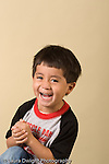 closeup headshot portrait of boy age 3 hands clasped laughing hard vertical