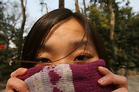 A Chinese woman hides her face with a colourful glove.<br />