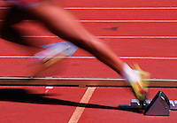 Detail action image of a runner's legs as s he leaves the starting block.