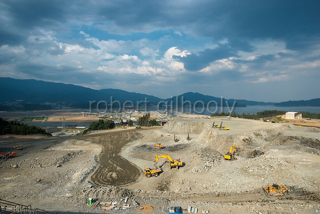 Photo shows the view from a hilltop overlooking Rikuzentakata, Iwate Prefecture, Japan. Atlas Copco drill rigs are a key feature of the project, which will shift blasted rubble from a nearby hillside to the central part of the city, which was flattened by the 2011 tsunami, where the land will be raised 10 meters. Rubble is transferred to the lower lying coastal land via a 3-km-long conveyor belt system. Rob Gilhooly Photo