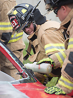 NWA Democrat-Gazette/J.T. WAMPLER Rogers firefighter Travis Harp saws Wednesday Sept. 9, 2015 through a vehicle's frame during extrication exercises. The department does similar training  throughout the year as opportunities allow. The training allows firefighters to try out new techniques and keep familiar with the equipment used to remove vehicle occupants after accidents.